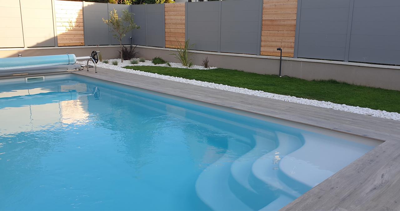 Piscine coque, terrasse carrelée, jardin paysagé, clôture alu/bois